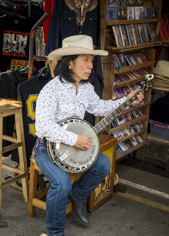 A Thai cowboy playing the banjo and selling leather boots and wallets at the market