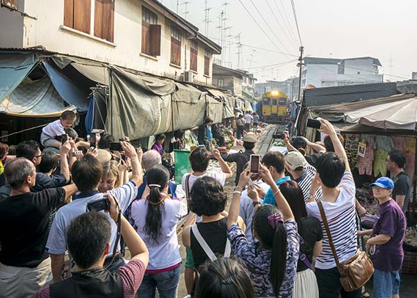 people photographing the train at the railroad market in Bangkok Thailand